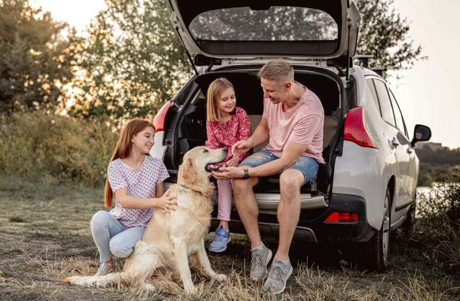Family Sitting in Trunk of SUV with Dog