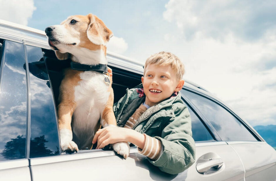 Child and Dog Riding in Car