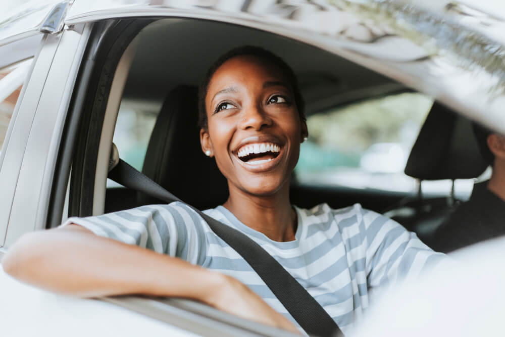 smiling woman in drivers seat of car