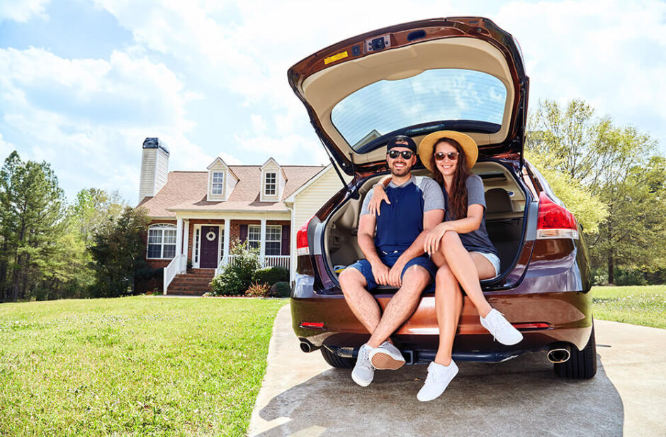 Couple in the back of a automobile in front of house