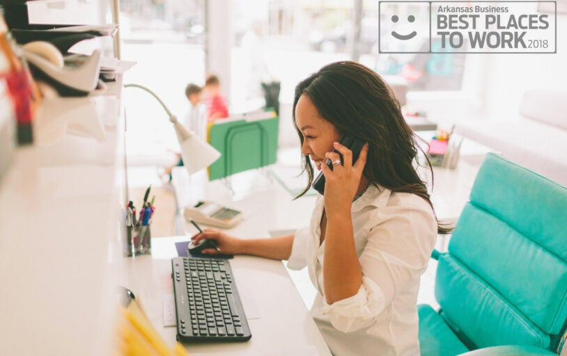 Women on a phone in front of a computer, Arkansas Business Best Places to Work 2018