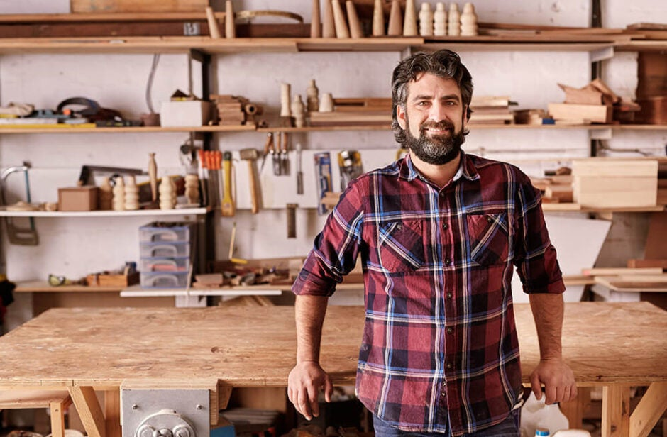 Man with a bread in a plaid shirt standing in wood working workshop