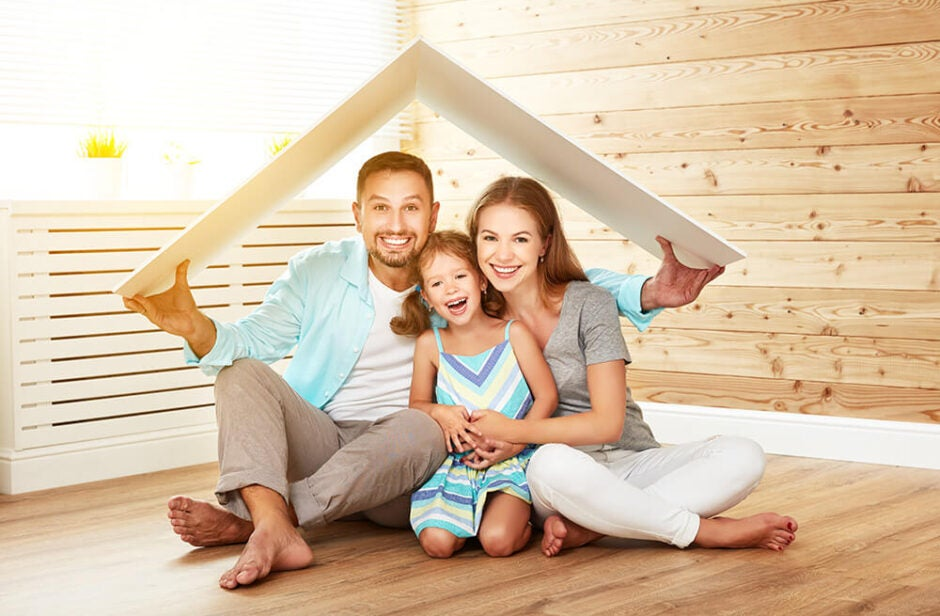Family of three sitting underneath a folded board in the shape of a top of a house