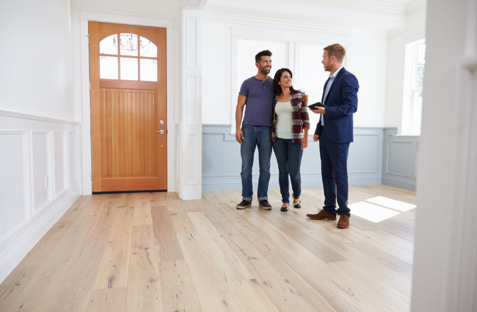 people in a new empty home with a realtor