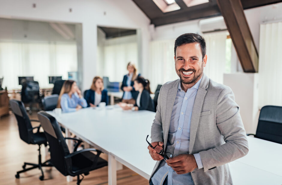 Man smiling at conference table in front of people